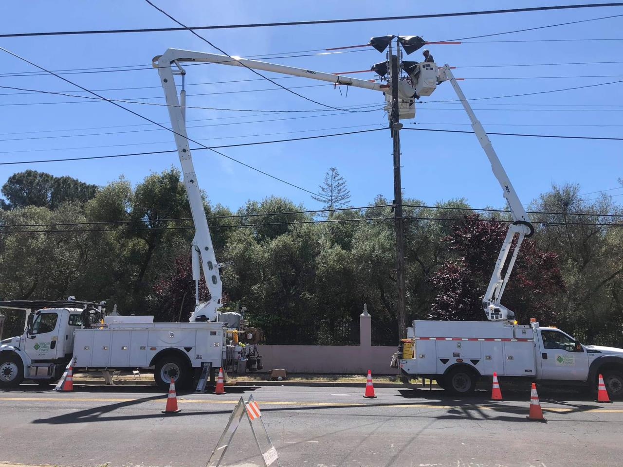 2 bucket trucks working on a power line
